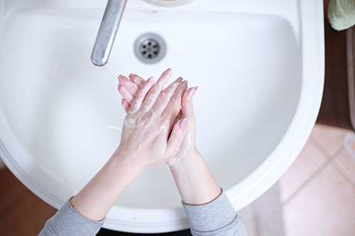 Overhead view of a woman washing her hands at a white bathroom sink