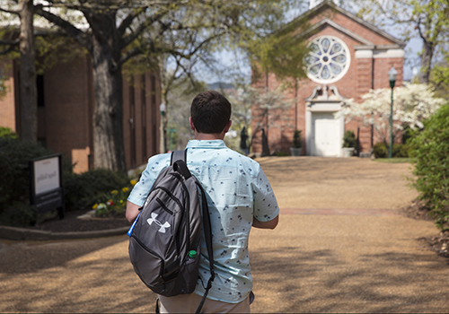 a male student walks towards the chapel carrying a backpack